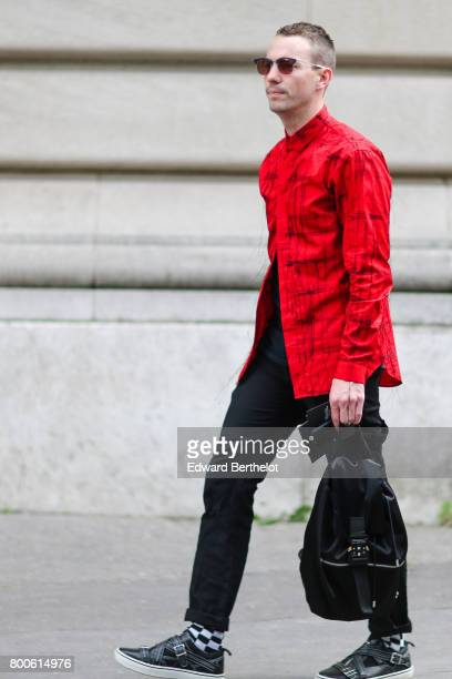 A guest wears a red shirt black pants gingham socks and shoes outside the Dior show during Paris Fashion Week Menswear Spring/Summer 2018 on June 24...