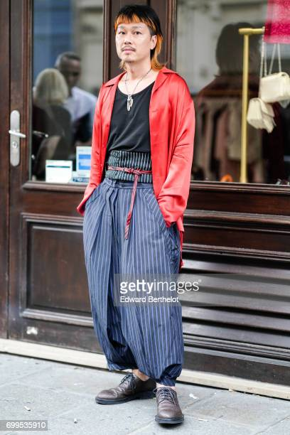 A guest wears a red silk shirt a black top oversized striped pants and leather shoes outside the Haider Ackermann show during Paris Fashion Week...
