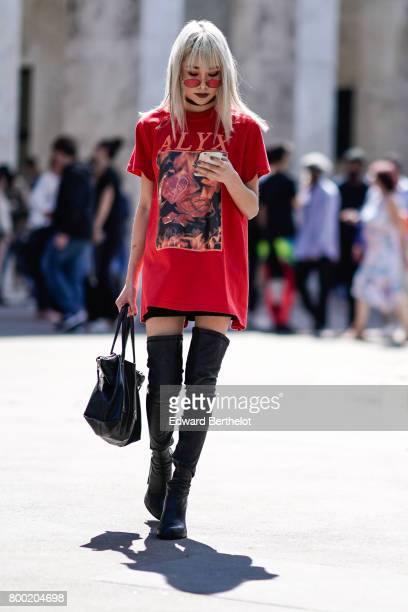 A guest wears a red top sunglasses and thigh high boots outside the Christian Dada show during Paris Fashion Week Menswear Spring/Summer 2018 on June...