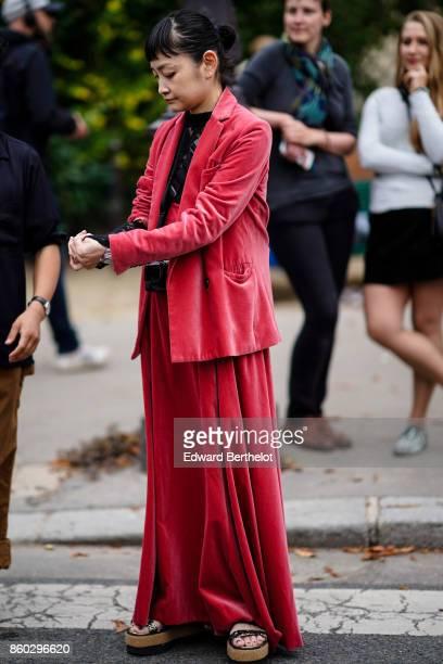 A guest wears a red velvet jacket a black lace top a red velvet oversize red skirt platform cork sandals outside Lanvin during Paris Fashion Week...