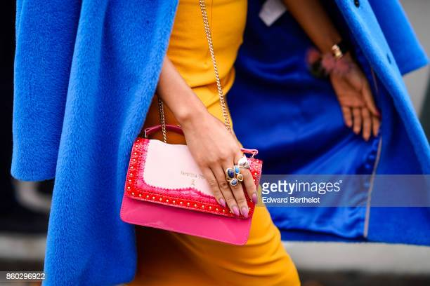 A guest wears a royal blue coat an ochre yellow dress a pink bag with red and white empiecements outside Lanvin during Paris Fashion Week Womenswear...