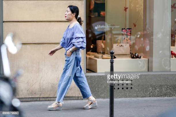 A guest wears a ruffled blue top flared jeans and silver shoes outside the OAMC show during Paris Fashion Week Menswear Spring/Summer 2018 on June 21...
