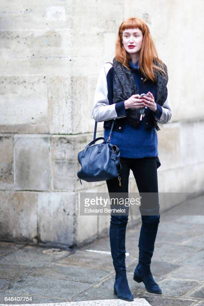 A guest wears a scarf a coat a blue pull over black pants a blue bag and blue thigh high boots outside the JOUR/NE show during Paris Fashion Week...