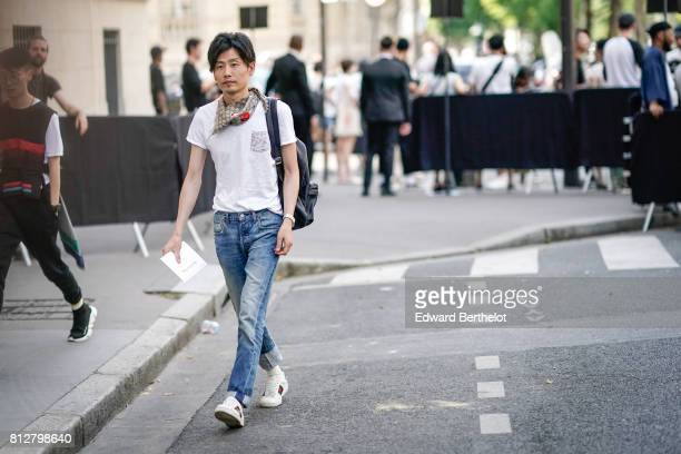 A guest wears a scarf a white shirt blue denim jeans white sneakers outside the Valentino show during Paris Fashion Week Menswear Spring/Summer 2018...