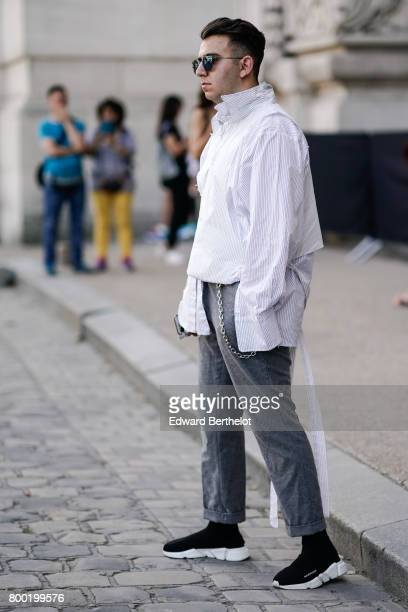 A guest wears a shirt gray pants black shoes outside the Cerruti show during Paris Fashion Week Menswear Spring/Summer 2018 on June 23 2017 in Paris...