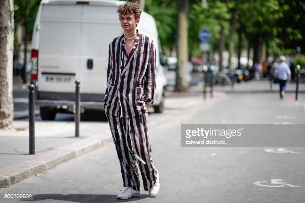 A guest wears a striped full outfit outside the 22/4 Hommes show during Paris Fashion Week Menswear Spring/Summer 2018 on June 23 2017 in Paris France