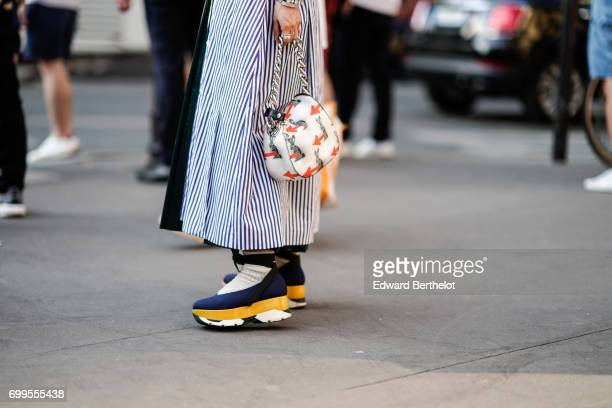 A guest wears a striped outfit sneakers shoes and a bag with prints outside the OAMC show during Paris Fashion Week Menswear Spring/Summer 2018 on...