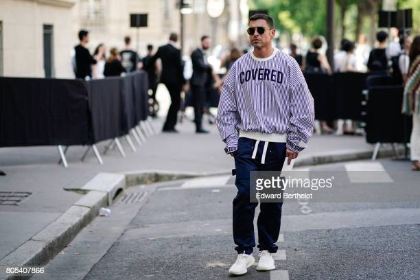 A guest wears a striped oversized pull over 'covered' blue pants white shoes outside the Valentino show during Paris Fashion Week Menswear...