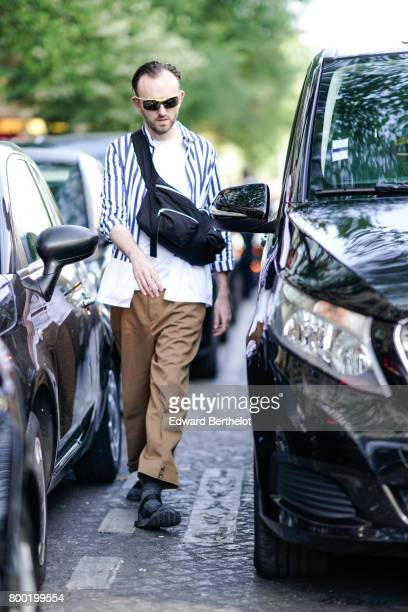A guest wears a striped shirt a white top brown pants after the CDG Comme des Garcons show during Paris Fashion Week Menswear Spring/Summer 2018 on...