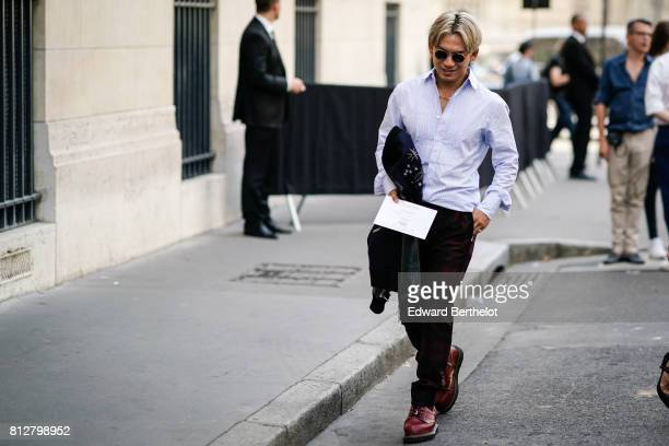 A guest wears a striped shirt black pants brown shoes sunglasses outside the Valentino show during Paris Fashion Week Menswear Spring/Summer 2018 on...