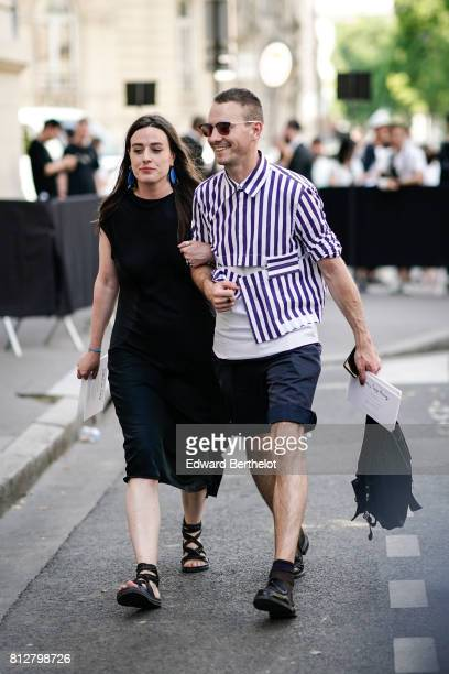 A guest wears a striped shirt sunglasses shorts black shoes a guest wears a black dress and gladiator sandals outside the Valentino show during Paris...