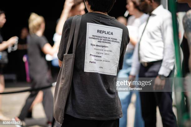 A guest wears a tshirt with a patch 'Replica' on the back outside the Y/Project show during Paris Fashion Week Menswear Spring/Summer 2018 on June 21...