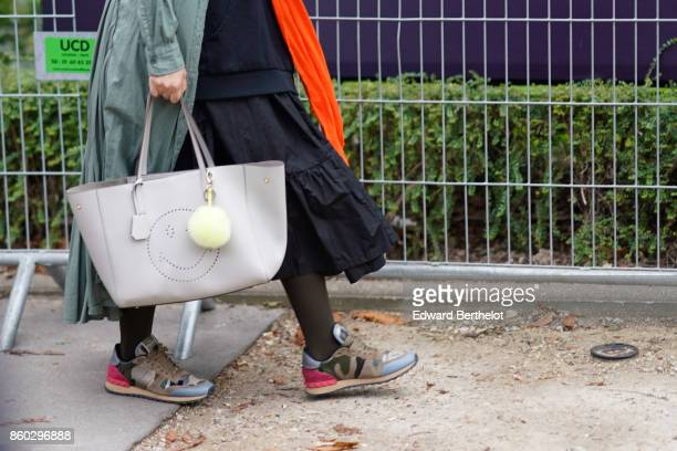A guest wears a verdigris trenchcoat a black gathered skirt a grey bag with a white bobble muticolor sneakers outside Lanvin during Paris Fashion...