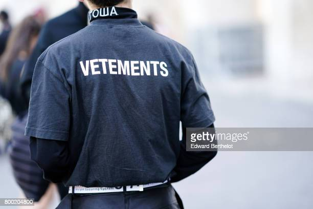 A guest wears a Vetements top outside the Christian Dada show during Paris Fashion Week Menswear Spring/Summer 2018 on June 23 2017 in Paris France
