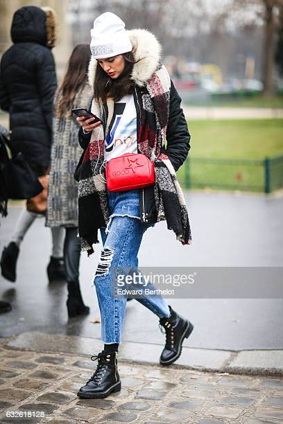 A guest wears a white beanie hat a checked scarf a redd bag blue denim ripped jeans and black shoes outside the Chanel show at the Grand Palais...