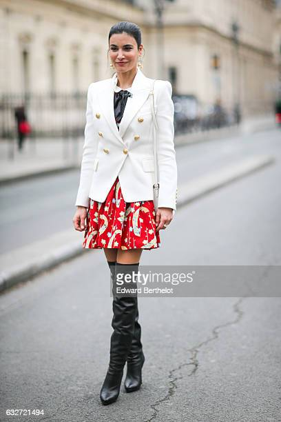 A guest wears a white blazer jacket a red skirt and black thigh high boots outside the Jean Paul Gaultier show during Paris Fashion Week Haute...
