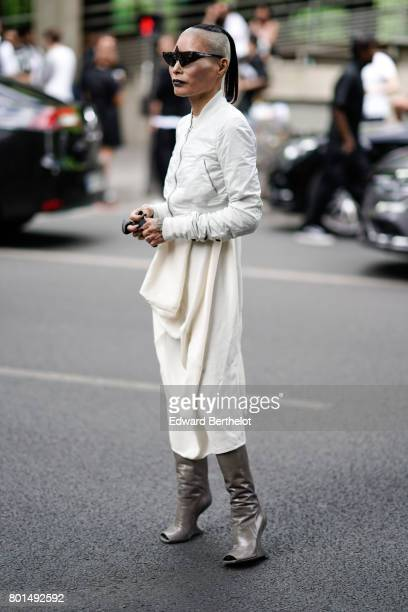 A guest wears a white bomber jacket sunglasses a white lace skirt shiny boots and has a shaved head outside the Y3 show during Paris Fashion Week...