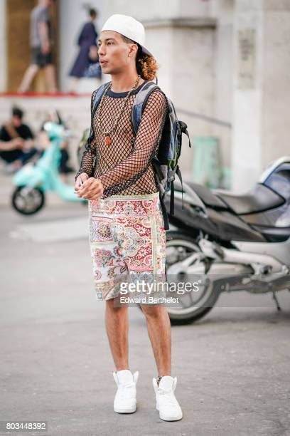 A guest wears a white cap a backpack a mesh top a colorful short white sneakers outside the 22/4 Hommes show during Paris Fashion Week Menswear...