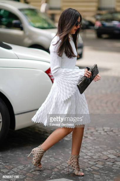 A guest wears a white dress heels a black clutch outside the Zuhair Murad during Paris Fashion Week Haute Couture Fall/Winter 20172018 on July 5 2017...