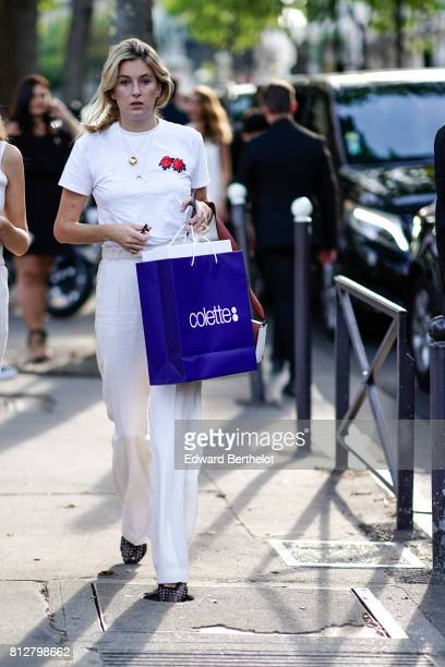 A guest wears a white floral print tshirt white pants outside the launch party for Chanel's new perfume 'Gabrielle' during Paris Fashion Week Haute...