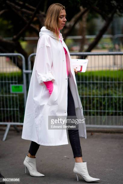 A guest wears a white hooded raincoat a pink top black pants white ankle boots outside Lanvin during Paris Fashion Week Womenswear Spring/Summer 2018...
