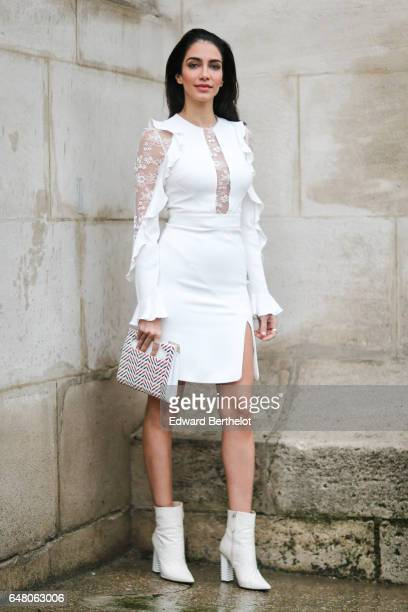 A guest wears a white lace dress a striped clutch and white boots outside the Elie Saab show during Paris Fashion Week Womenswear Fall/Winter...