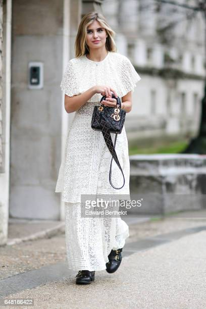 A guest wears a white lace dress and a Dior bag outside the Elie Saab show during Paris Fashion Week Womenswear Fall/Winter 2017/2018 on March 4 2017...
