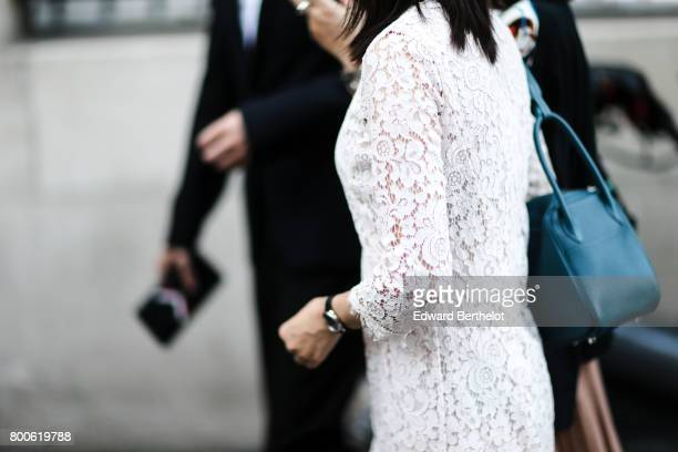 A guest wears a white lace dress outside the Hermes show during Paris Fashion Week Menswear Spring/Summer 2018 on June 24 2017 in Paris France