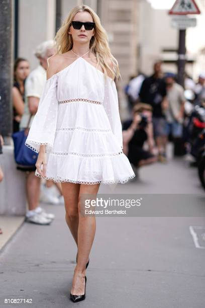 A guest wears a white lace dress sunglasses and black heels shoes outside the Elie Saab show during Paris Fashion Week Haute Couture Fall/Winter...