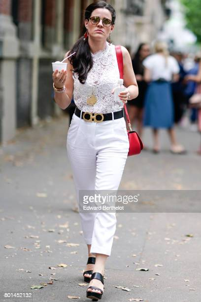 A guest wears a white lace top white pants a red bag and is holding an ice cream cup outside the Paul Smith show during Paris Fashion Week Menswear...