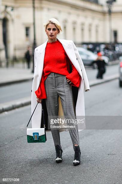 A guest wears a white long coat a red top gray pants a white and green bag outside the Jean Paul Gaultier show during Paris Fashion Week Haute...