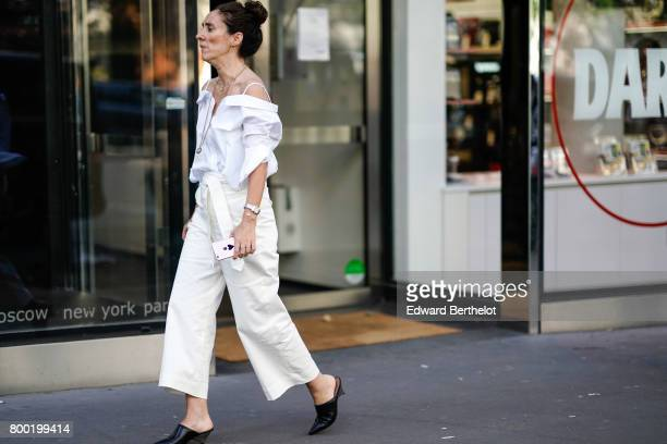 A guest wears a white off shoulder top white large pants and black shoes after the CDG Comme des Garcons show during Paris Fashion Week Menswear...