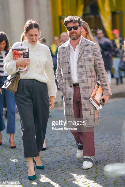A guest wears a white pull over black flare pants green shoes a guest wears sunglasses a tartan coat a white shirt cropped pants sneakers outside Miu...