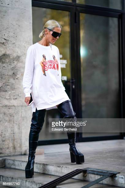 A guest wears a white pull over black leather pants outside the Lemaire show during Paris Fashion Week Womenswear Spring/Summer 2018 on September 27...