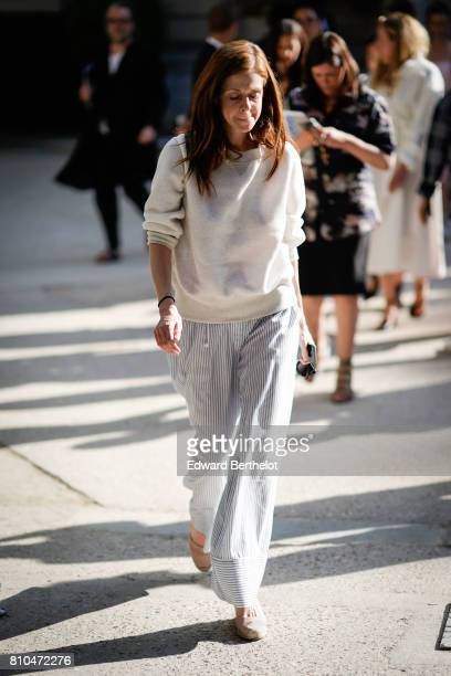 A guest wears a white pull over striped pants outside the Valentino during Paris Fashion Week Haute Couture Fall/Winter 20172018 on July 5 2017 in...