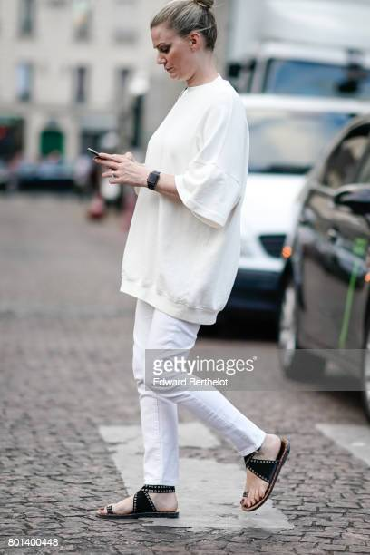 A guest wears a white pull over white pants sandals outside the Kenzo show during Paris Fashion Week Menswear Spring/Summer 2018 on June 25 2017 in...