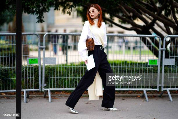 A guest wears a white pull over with ong sleeves black pants a brown fur bag silver shoes outside Lanvin during Paris Fashion Week Womenswear...
