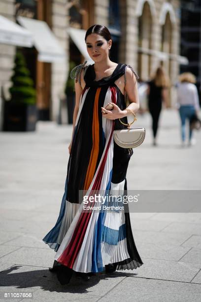A guest wears a white semicircular bag a long ruffle multicolor stripe dress outside Alexis Mabille during Paris Fashion Week Haute Couture...