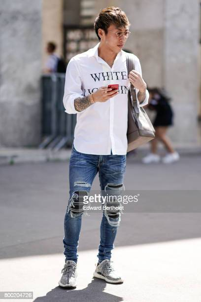 A guest wears a white shirt and ripped jeans outside the Christian Dada show during Paris Fashion Week Menswear Spring/Summer 2018 on June 23 2017 in...