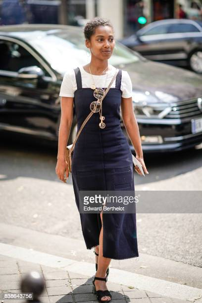 A guest wears a white tshirt a blue dress black shoes sunglasses a clutch outside the Y/Project show during Paris Fashion Week Menswear Spring/Summer...