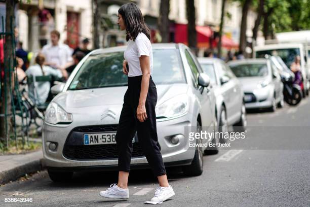 A guest wears a white tshirt black cropped pants white sneakers outside the Y/Project show during Paris Fashion Week Menswear Spring/Summer 2018 on...