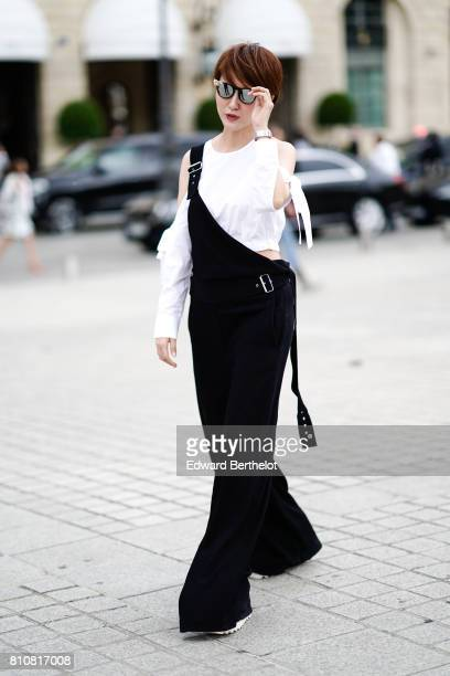 A guest wears a white tshirt mirror sunglasses a black jumpsuit with flared pants outside the Schiaparelli show during Paris Fashion Week Haute...