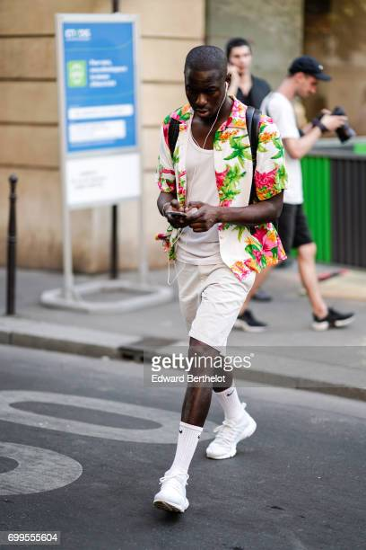 A guest wears a white tshirt white shorts white socks white sneakers shoes and a flower print shirt outside the OAMC show during Paris Fashion Week...