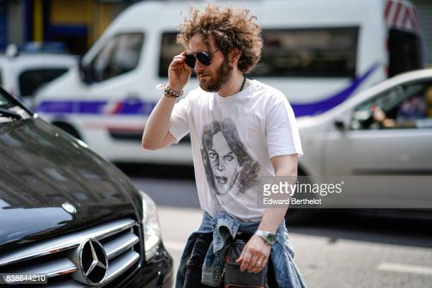 A guest wears a white tshirt with a drawn face a blue denim shirt outside the Y/Project show during Paris Fashion Week Menswear Spring/Summer 2018 on...