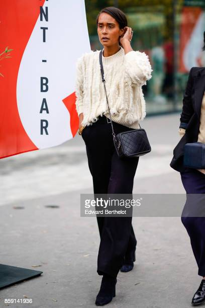 A guest wears a white wool pull over black pants black bag and boots outside Ann Demeulemeester during Paris Fashion Week Womenswear Spring/Summer...