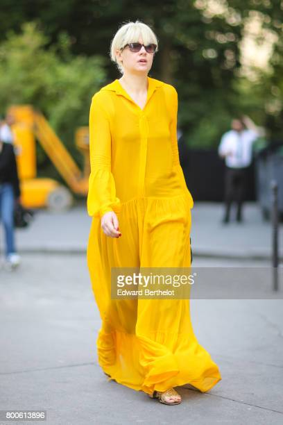 A guest wears a yellow dress outside the Dior show during Paris Fashion Week Menswear Spring/Summer 2018 on June 24 2017 in Paris France