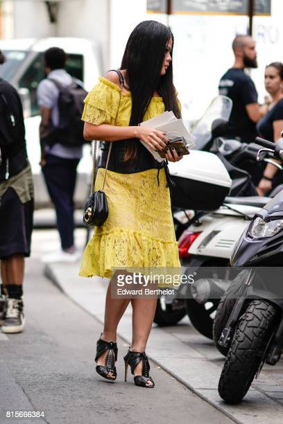 A guest wears a yellow ruffle dres a black leather bag black heels outside the Elie Saab show during Paris Fashion Week Haute Couture Fall/Winter...