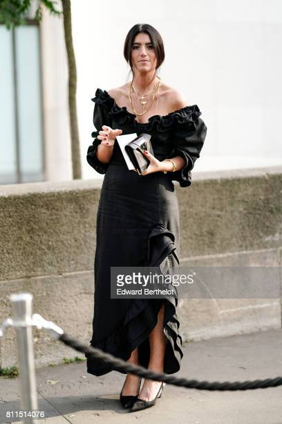 A guest wears an offshoulder black dress with ruffle outside the launch party for Chanel's new perfume 'Gabrielle' during Paris Fashion Week Haute...