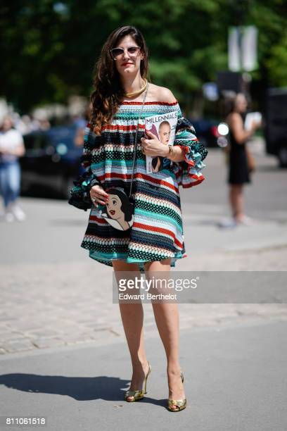 A guest wears an offshoulder strapless striped multicolor short dress with ruffle sleeves white sunglasses a bag with the Disney character Snow White...