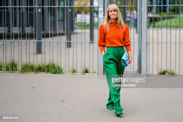 A guest wears an orange pull over and green pants outside Carven during Paris Fashion Week Womenswear Spring/Summer 2018 on September 28 2017 in...